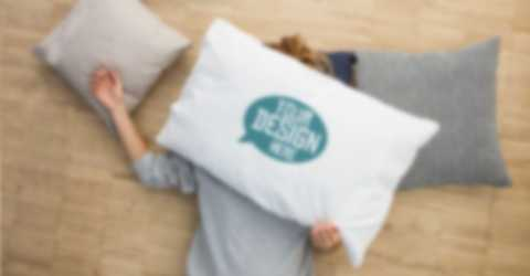 Two women hide their faces behind custom pillow cases