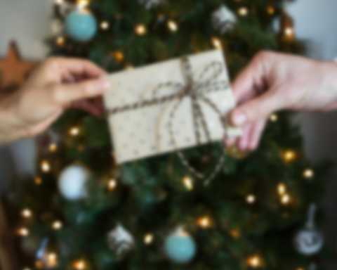 Two people exchanging gift certificate in front of Christmas tree.