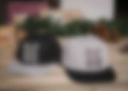 Deux casquettes Snapback personnalisées posées entourées de décorations de Noël