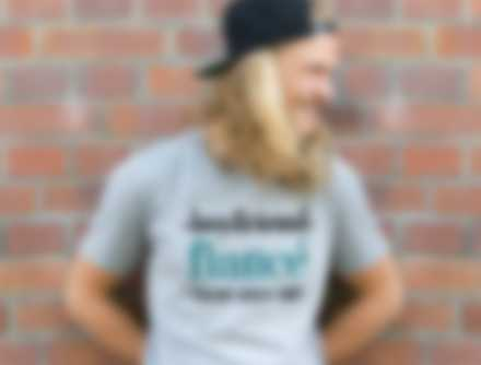 Man standing against brick wall while wearing a personalized t-shirt.