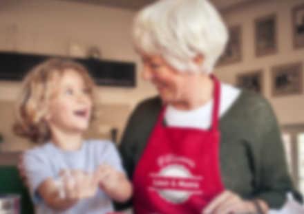 Avec son tablier personnalisé, une grand-mère cuisine avec son petit-fils
