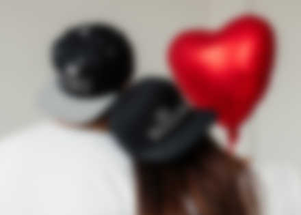 Couple wearing custom caps with Valentine\'s design.