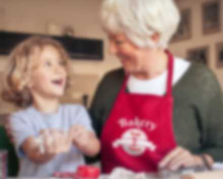 Grandmother and child have fun in the kitchen while grandmother wears a personalized apron.