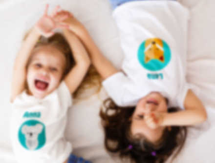 Two smiling children laughing in a bed while wearing customized t-shirts.