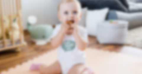 La mine réjouie, un bébé fait de grands yeux dans un cache-couche personnalisé.