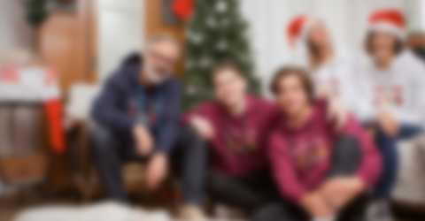 Une famille posant devant le sapin de Noël et portant un molleton à capuche personnalisé