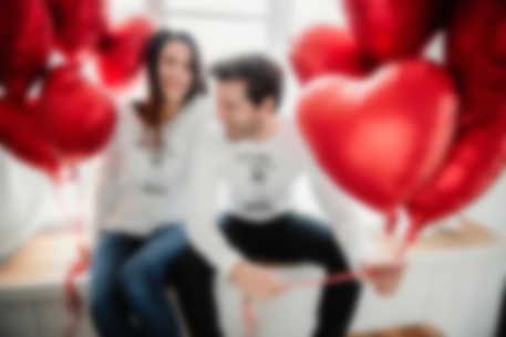 Un couple homme femme trinquant à l\'amour avec un mug personnalisé.
