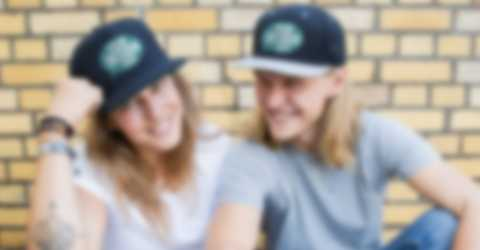 Couple sitting in front of a wall and wearing custom hats