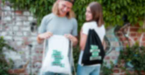Un jeune homme et une jeune femme portant des sacs de sport à cordon personnalisés