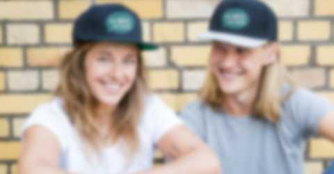 Devant un mur, un couple avec leurs tuques personnalisées