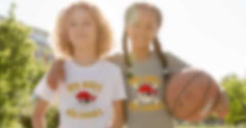 Après un match de basquet, deux enfants posent fièrement avec leurs t-shirts personnalisés