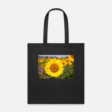 Field Sunflower flower head sticks out in a field - Tote Bag